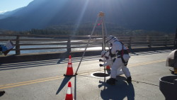 Workers prepare to enter this confined space below the roadway of a bridge